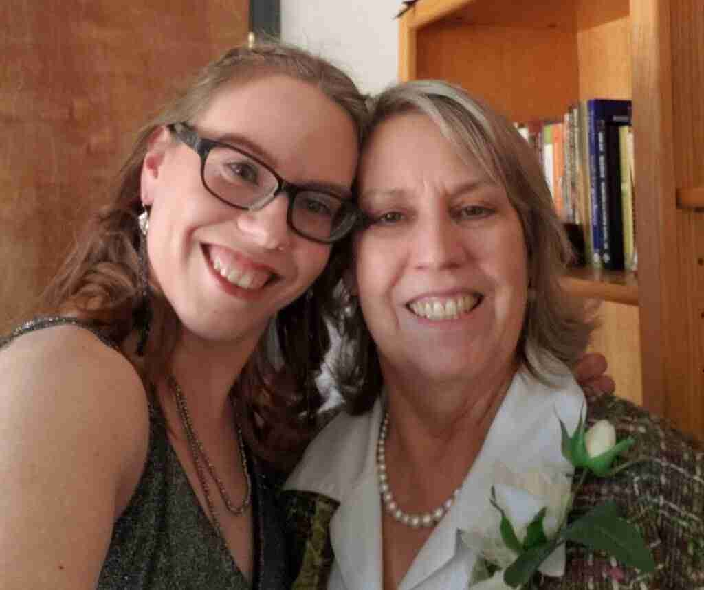 young woman and mother smiling at camera