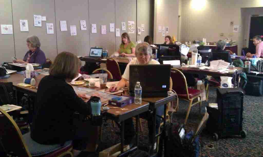 women working on computers and photo albums at workshop